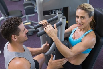 Personal trainer coaching smiling female bodybuilder using weigh