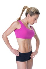 Female bodybuilder posing in pink sports bra