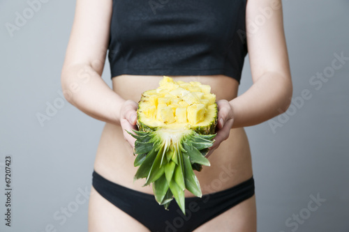 Young woman's body with pineapple