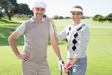 Golfing couple smiling at camera and holding clubs