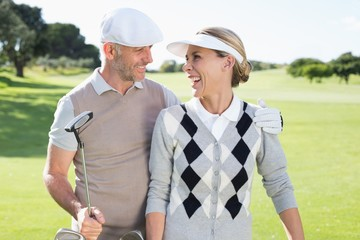 Golfing couple smiling at each other on the putting green