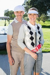 Happy golfing couple looking at camera with golf buggy behind