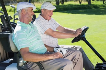 Golfing friends laughing together in their golf buggy