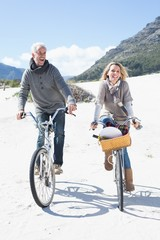 Carefree couple going for a bike ride and picnic on the beach