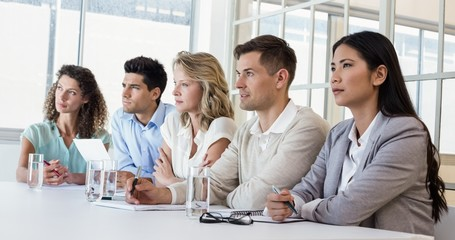 Casual business team listening during meeting