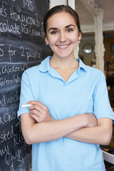 Waitress In Restaurant Writing Menu On Blackboard