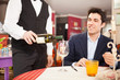 Waiter serving some wine to a man in a restaurant