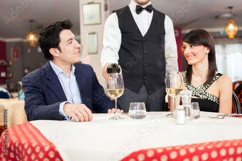 canvas print picture Waiter pouring wine to a couple