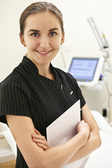 Portrait Of Beautician Standing By Laser Treatment Equipment