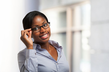 Smiling black woman holding her eyeglasses