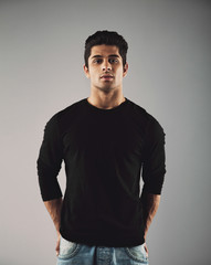 Handsome young hispanic guy posing on grey background