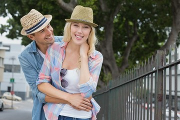Hip young couple smiling at camera by railings