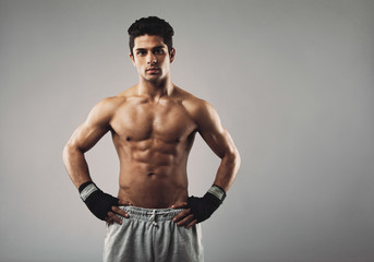 Strong young male boxer on grey background