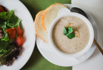 Fresh mushroom cream soup with bread on a table