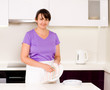 Smiling housewife cleaning the dinner plates