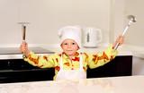 Cute boy chef displaying his utensils
