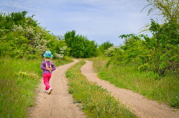 Small girl in a colorful outfit on a country track