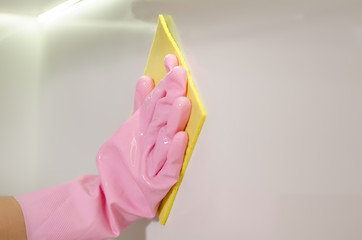 Gloved hand wiping a white surface with a cloth