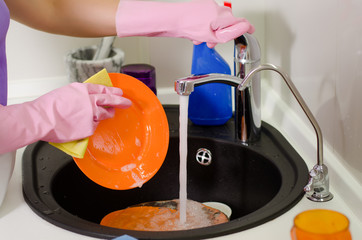 Woman rinsing plates under the tap