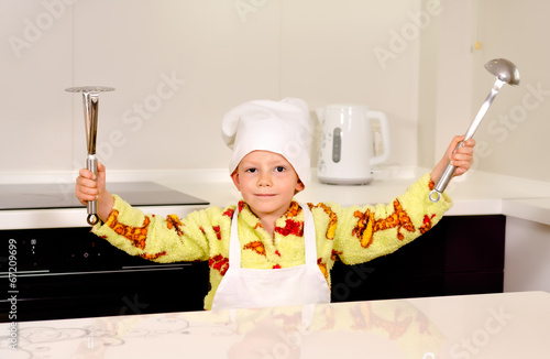 Cute boy chef displaying his utensils