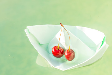 paper boat and fresh cherry