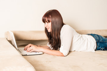 woman lying on the sofa with laptop