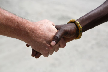 Handshake between a Caucasian and an African