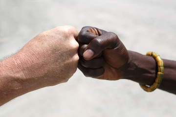 Hand greeting between a Caucasian and an African