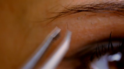 Part of face woman plucking eyebrows depilating with tweezers