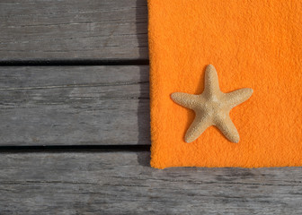 Beach towel and starfish on wood background