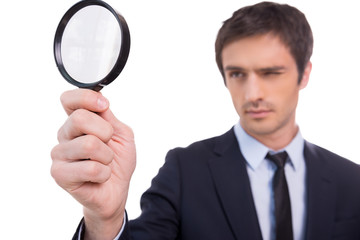 Looking through magnifying glass.