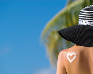 Woman with heart shaped sun cream