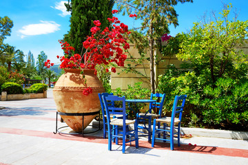 The amphora with flowers and traditional Greek table and chairs