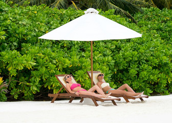 Beautiful girls relaxing on a beach chair near the sea