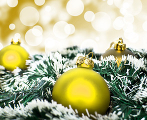 Yellow christmas ornament ball against yellow bokeh background