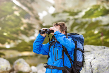Senior hiker with binoculars