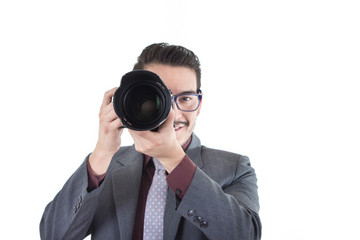 young man in suit looking through a camera