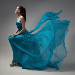 Fashion woman in fluttering blue dress. Gray background.
