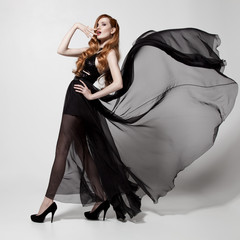 Fashion woman in fluttering black dress. White background.