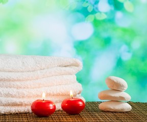 Spa massage border with towel stacked,red candles and stone