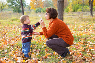 Boy with his mother in autum park