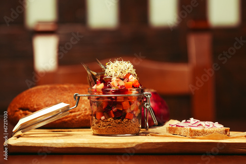 Mason jar with salad: pieces of vegetables and anchovy
