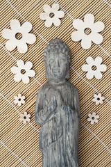 Stenen  grijze Boeddha met houten bloemen