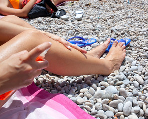 Woman applying suntan lotion oil to her body