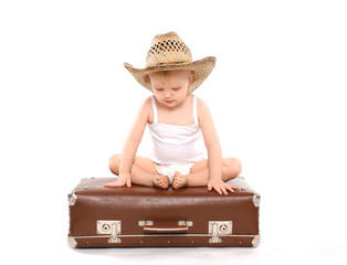 Little child in a straw summer hat sitting on the suitcase, trav