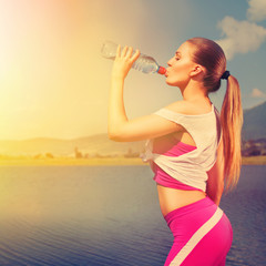 Young runner woman drinking water outdoors in summer