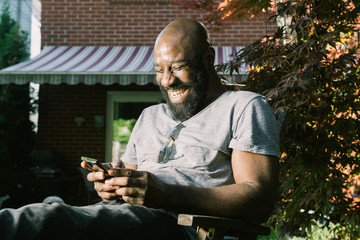 Man Laughs Reading Text Message in Garden