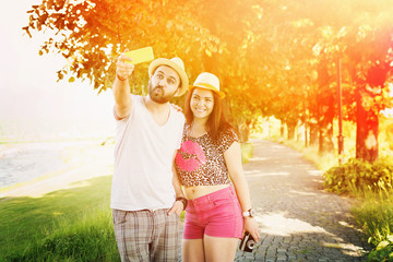 Young hipster couple taking a selfie outdoors in summer
