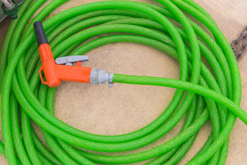 green with orange spray hose at the end of