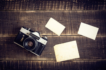 Old camera with empty photographs on wooden table